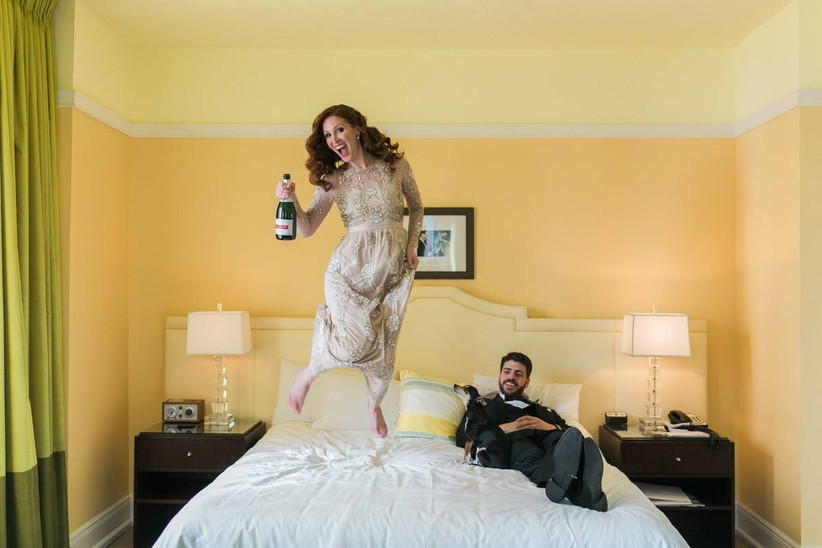 woman in evening gown jumping on bed while man in tuxedo and dog lies on bed