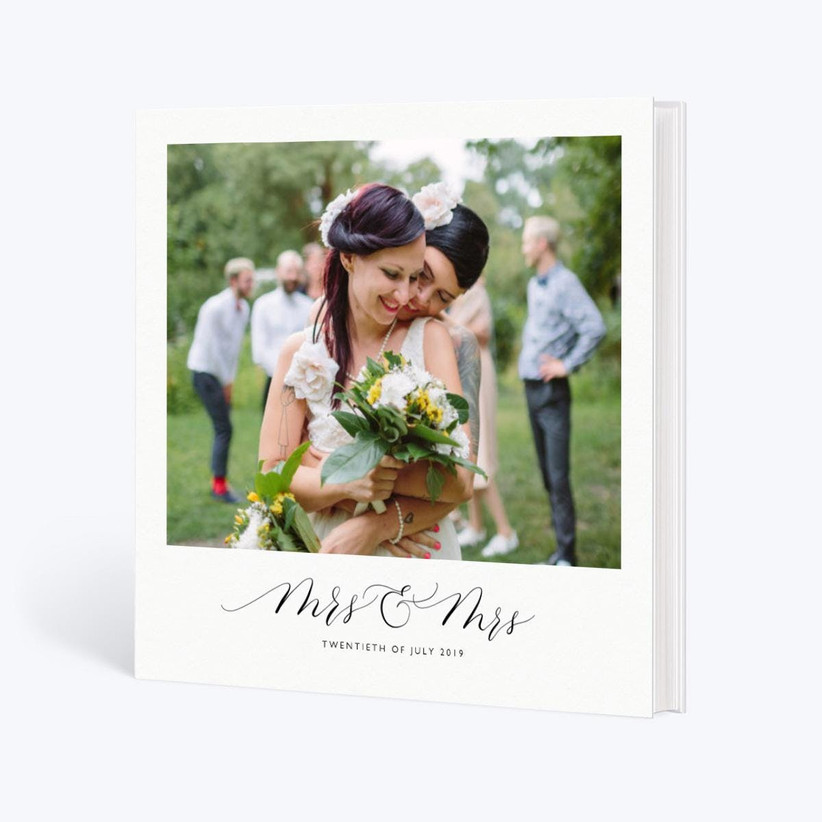 White wedding photo book with large photo of two brides on the cover with Mrs and Mrs and wedding date written below