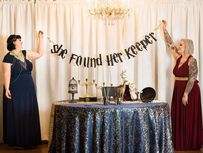 Two women holding up a bachelorette party banner that reads: She found her keeper