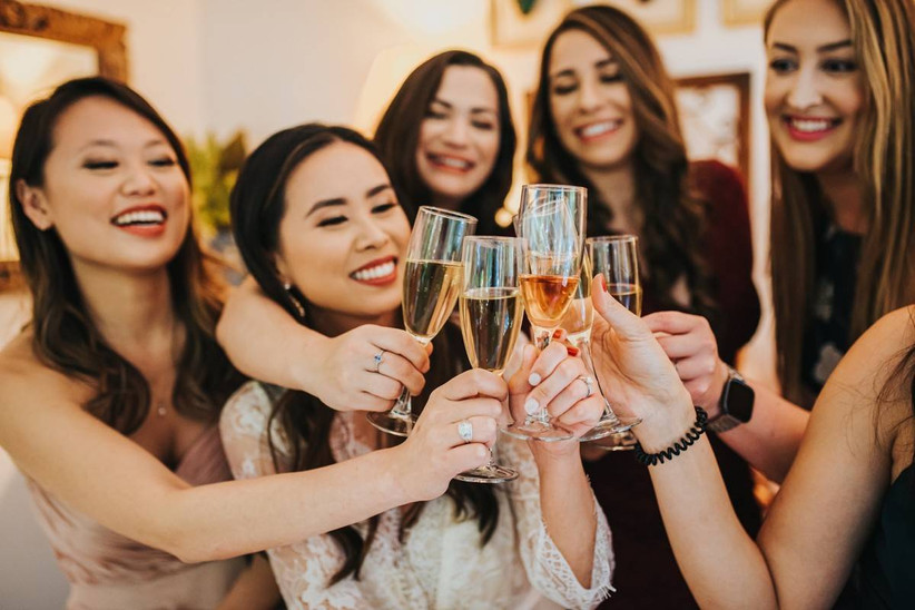 Smiling asian bride surrounded by friends toasting with glasses of champagne