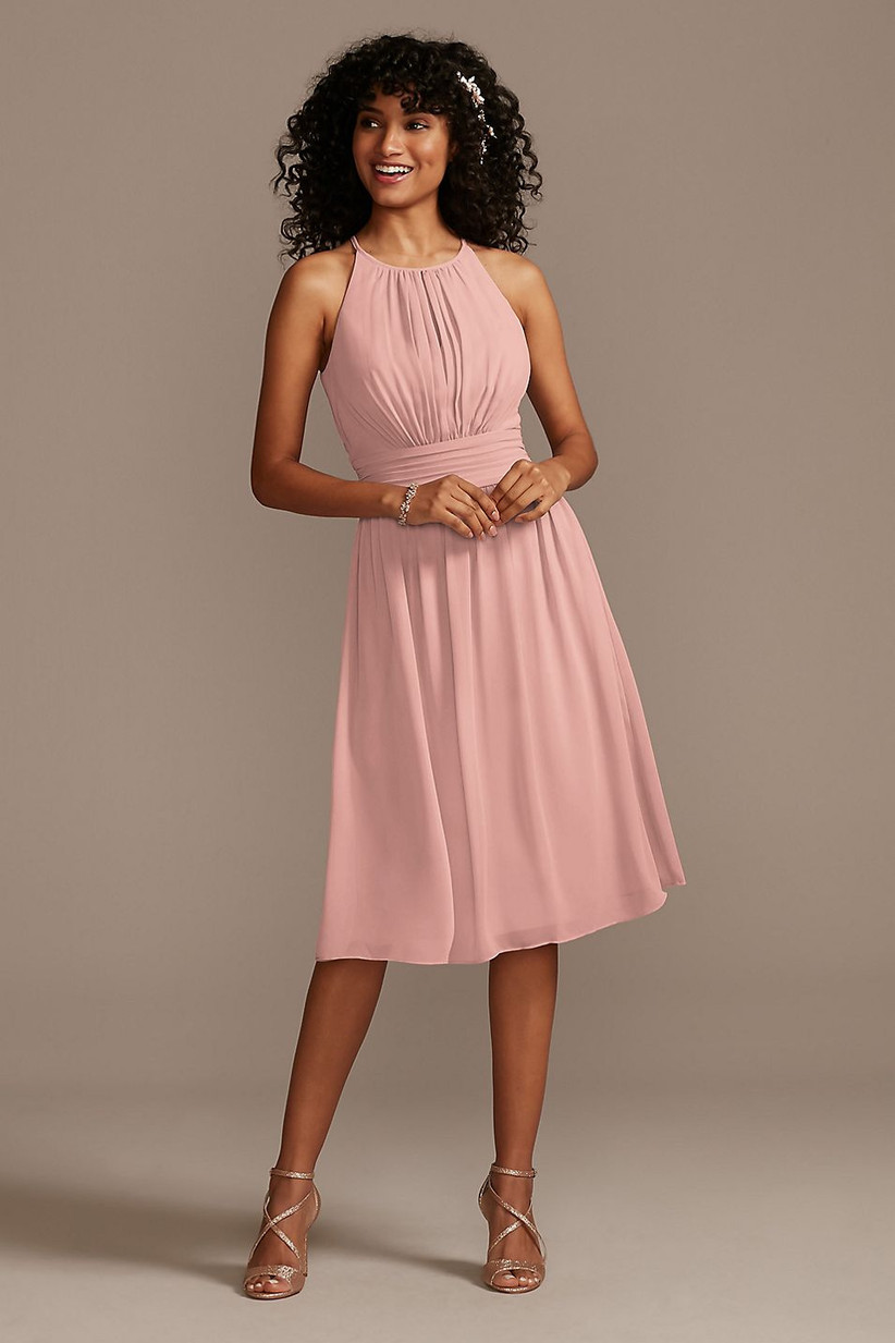 Model wearing short pastel pink bridesmaid dress with pleats