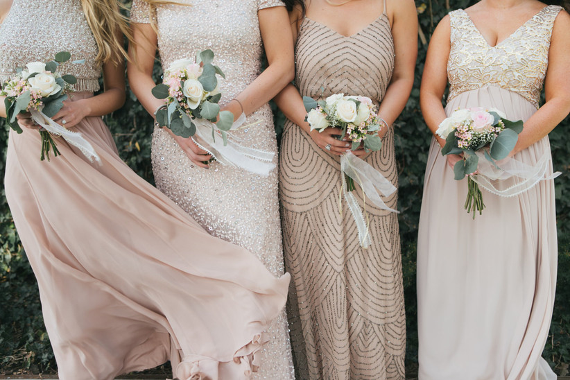bridesmaids wearing gold dresses and carrying small white bouquets