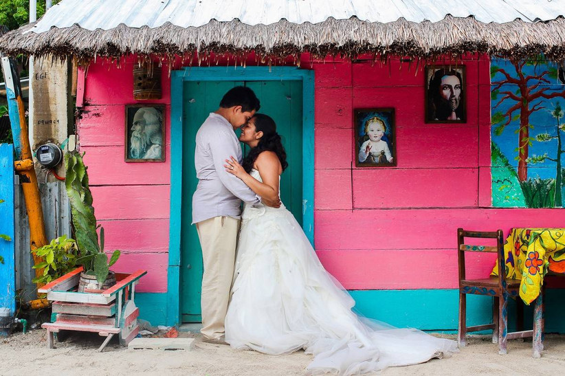 bride and groom hugging in front of a bright pink house