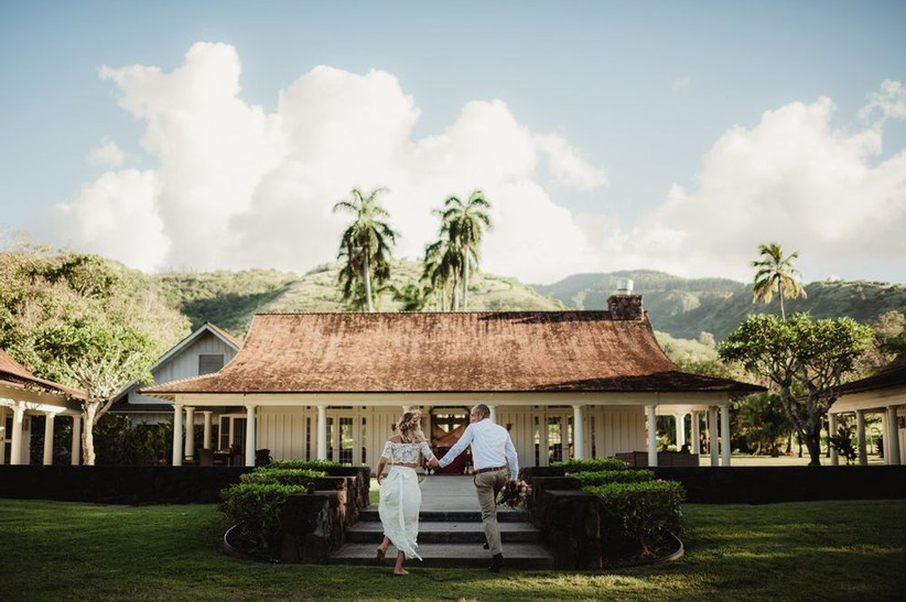 bride and groom walk up garden steps to pavilion wedding venue with mountain scenery and palm trees in the background