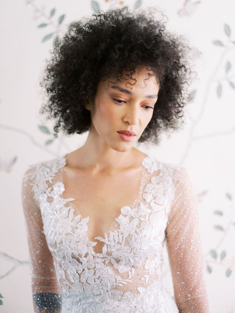 Black bride in beaded lace wedding dress with natural curly hair and soft pink makeup