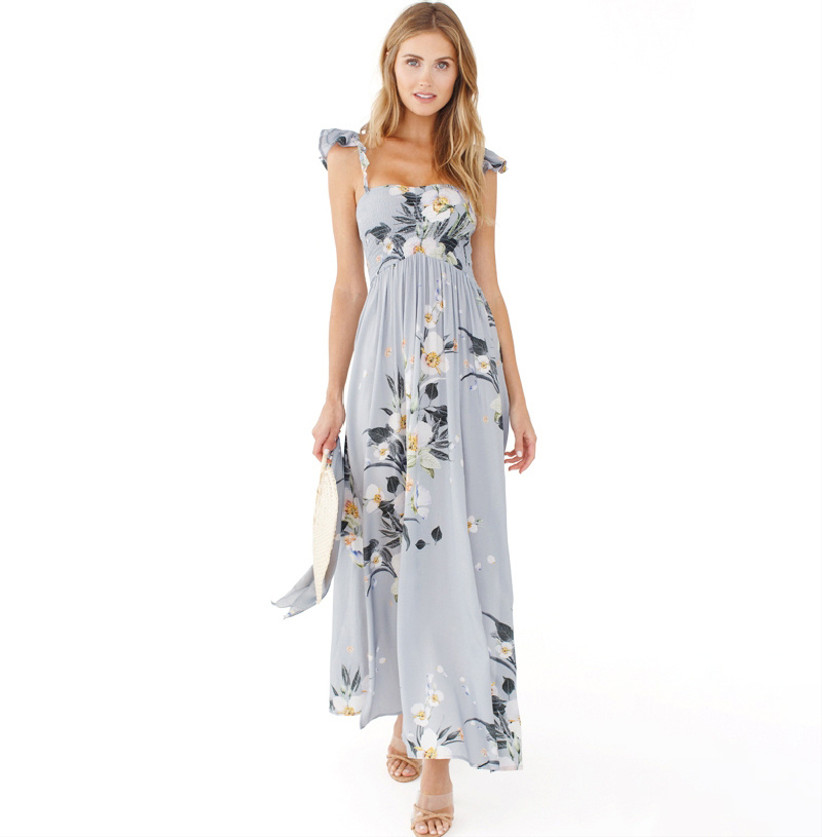 Model wearing floaty light blue maxi with white and green floral print