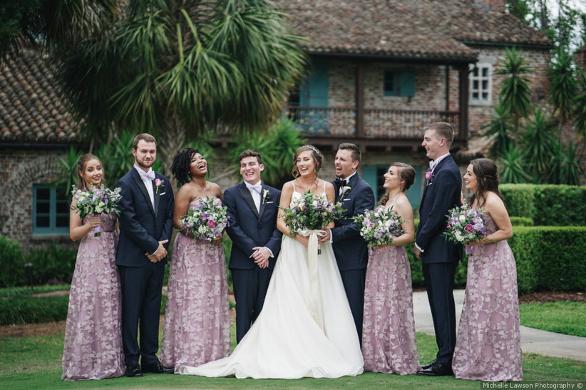 Wedding party photo with bridesmaids wearing patterned purple dresses