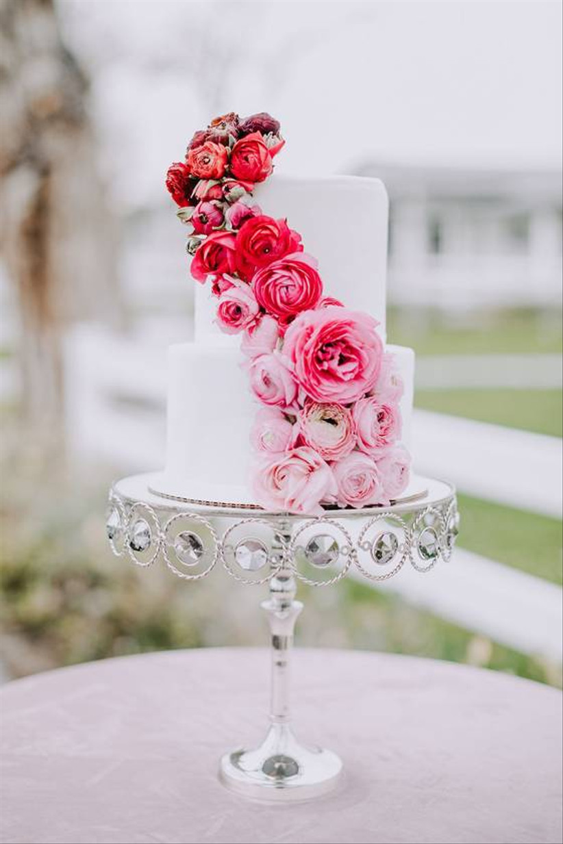 white wedding cake decorated with vibrant pink and red flowers