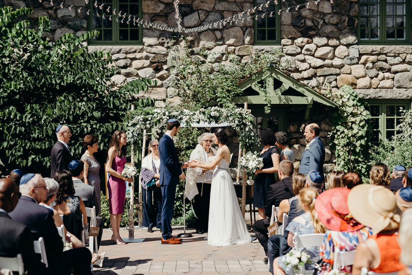 couple stands under chuppah made from birch branches and decorated with flowers