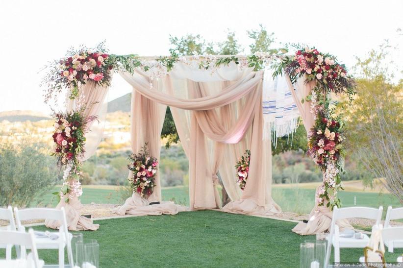 romantic & dramatic wedding chuppah with pink fabric and greenery