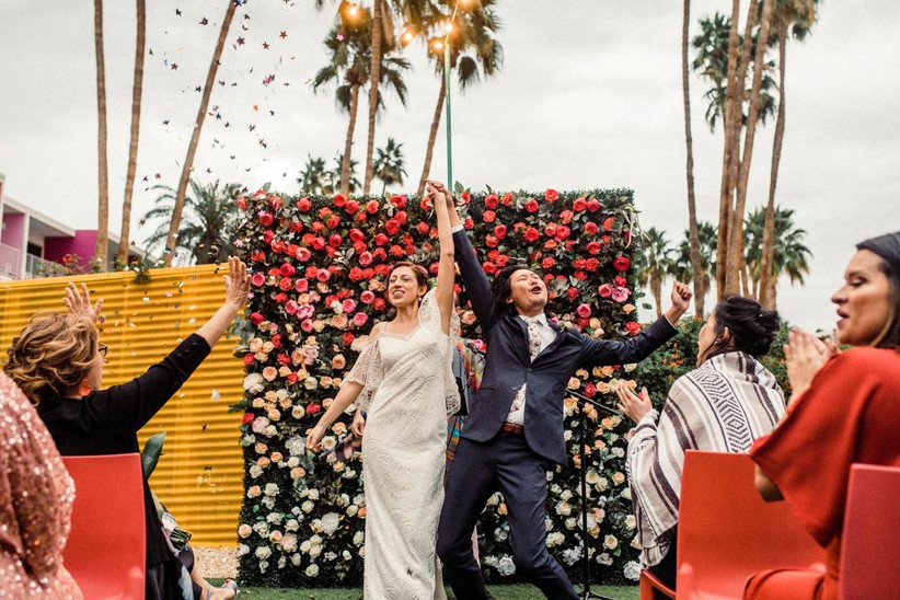 couple celebrating after wedding ceremony with colorful floral backdrop