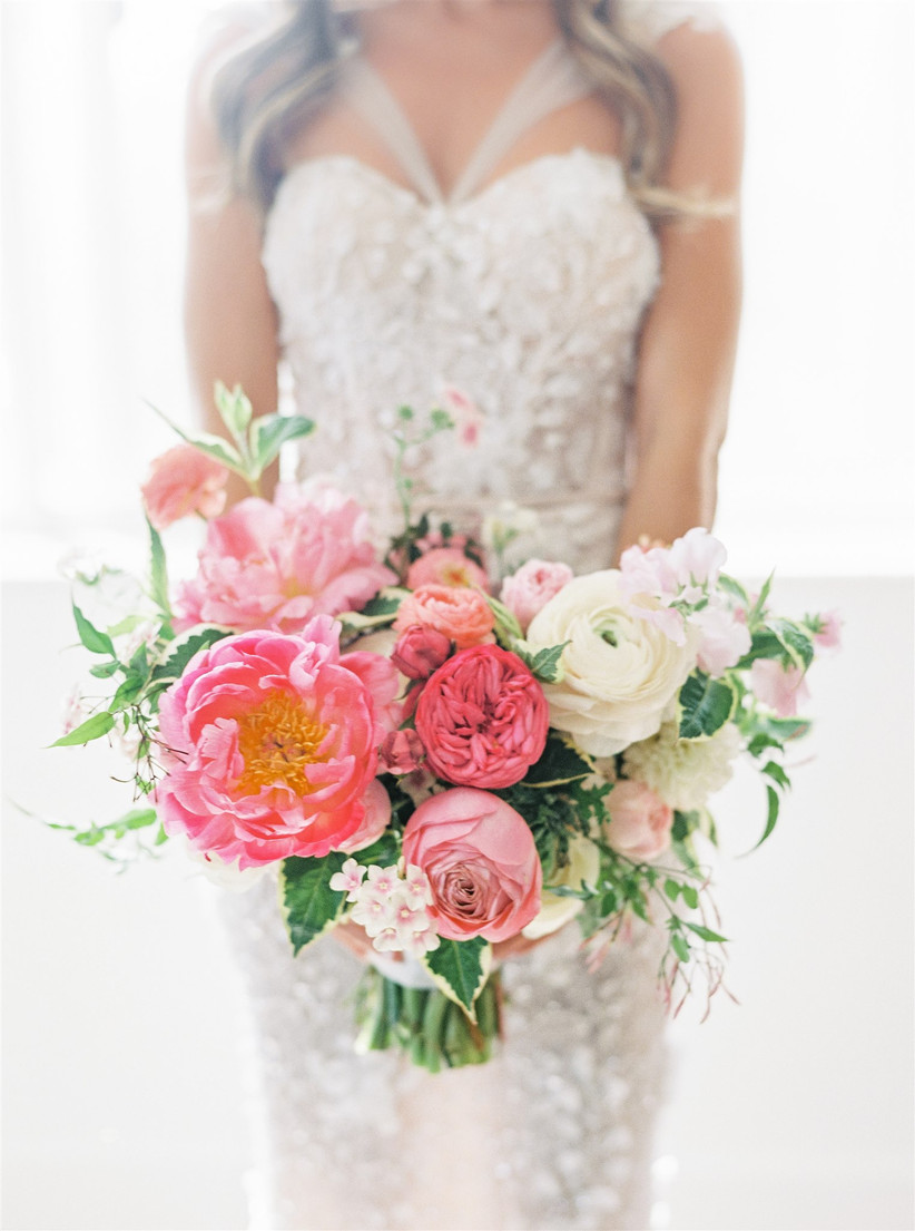 bride holds summer wedding bouquet with coral charm peonies
