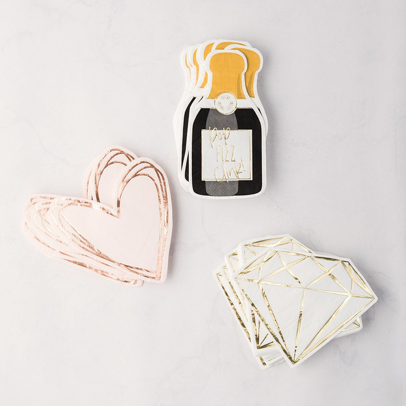Three stacks of napkins in different designs, including hearts, diamonds, and champagne bottles