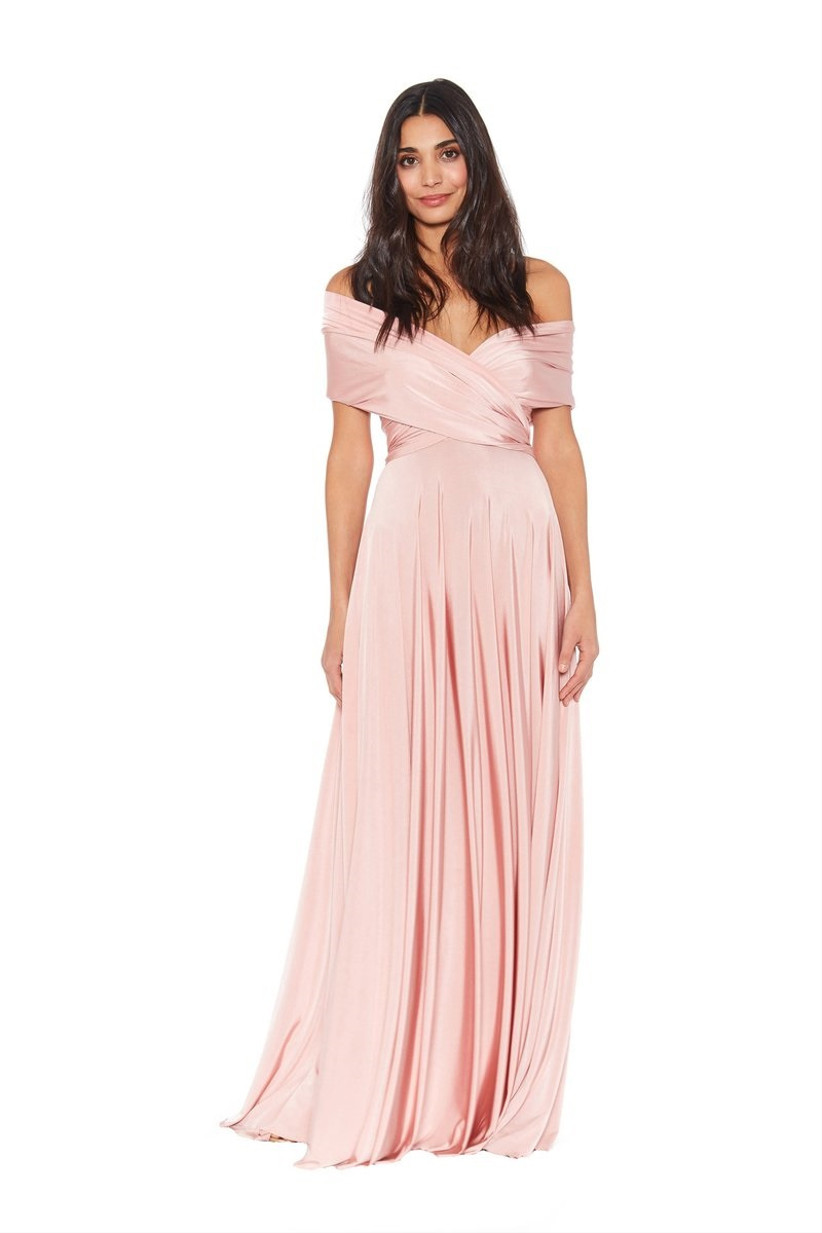 Model wearing convertible pastel pink bridesmaid dress with off-the-shoulder wrap