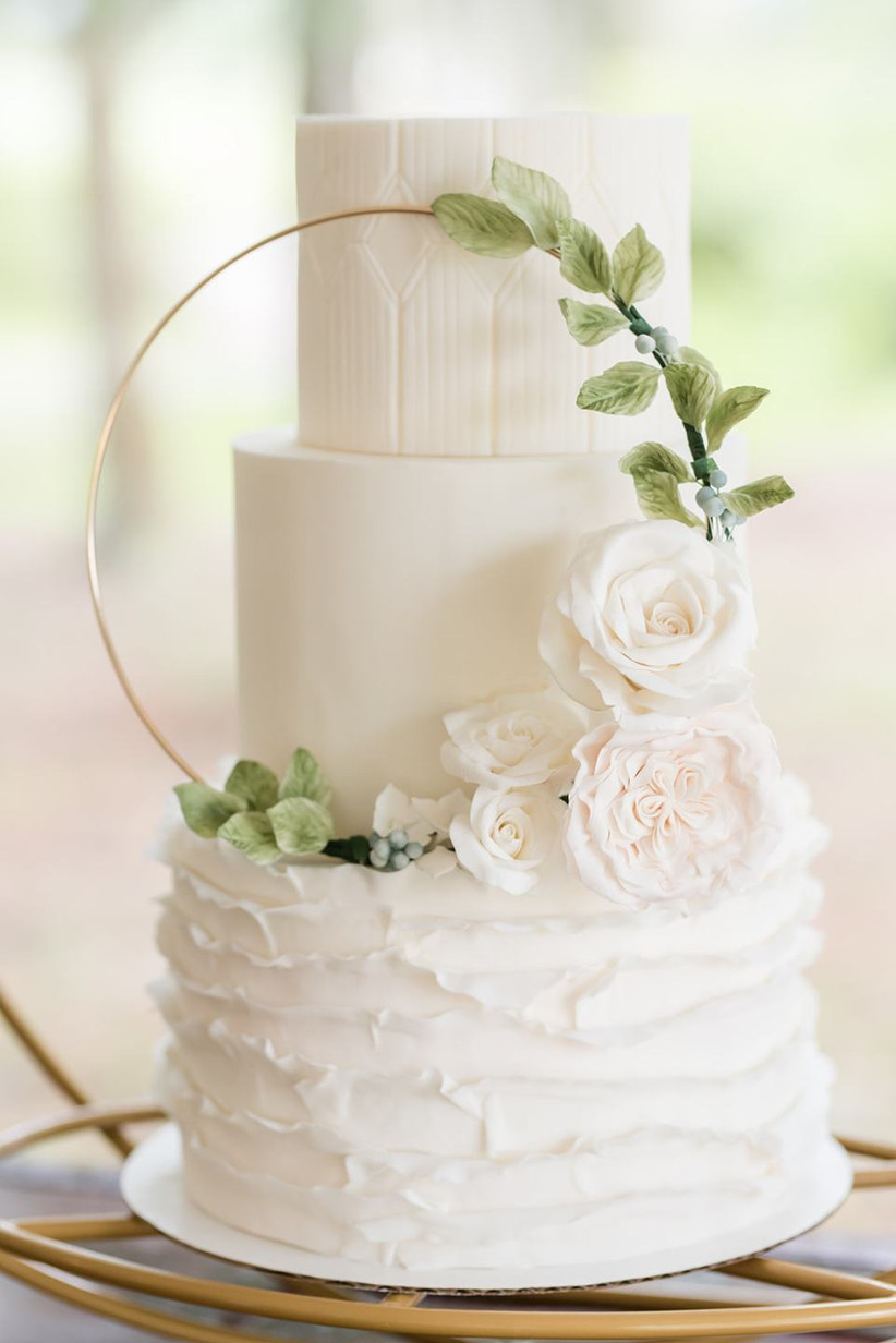 buttercream wedding cake decorated with sugar flowers and greenery showcased on a miniature wreath