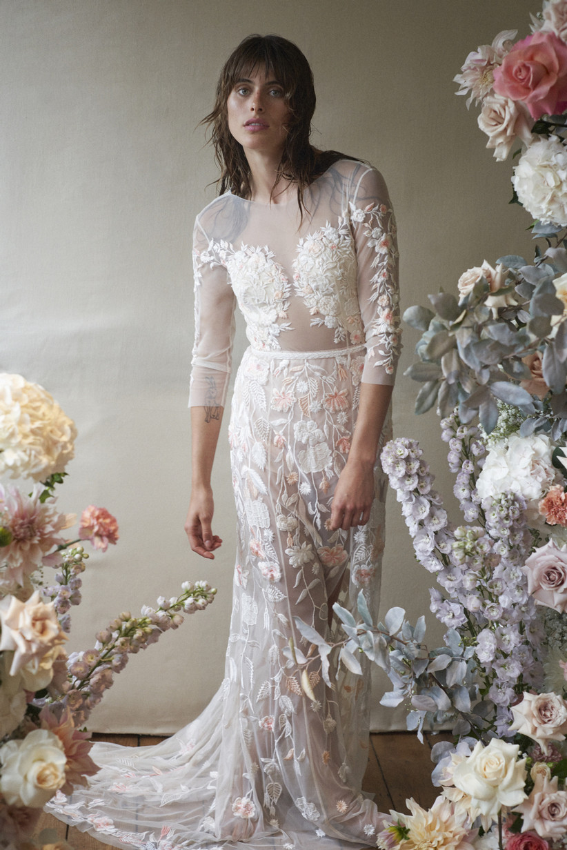 Bridal model wearing sheer embroidered wedding gown with colorful white and peach life-like flowers