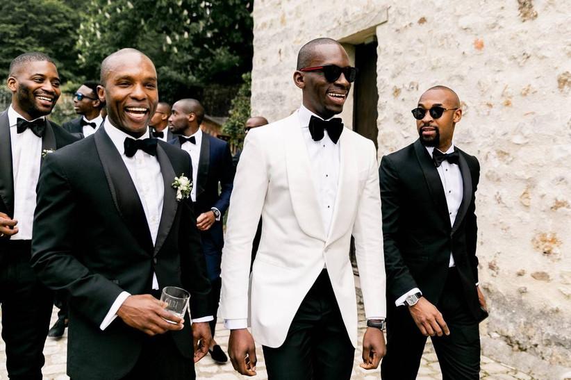Black groom and groomsmen walk through a cobblestone street while wearing tuxedos