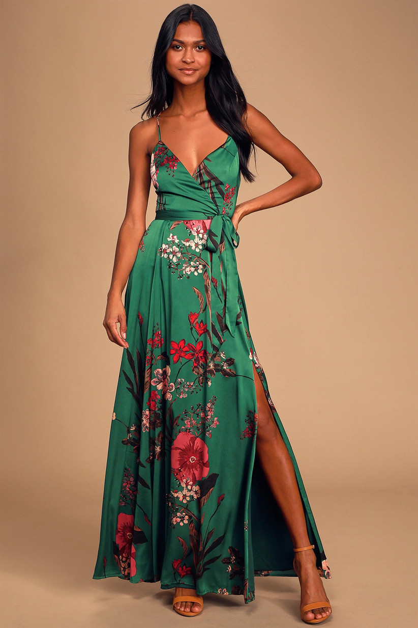 Model wearing emerald green maxi with bright red and pink floral pattern