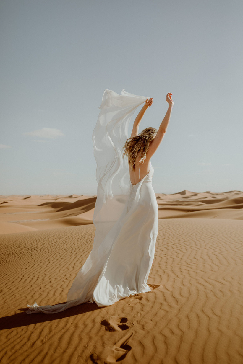 Model in the dessert facing away from camera wearing flowy wedding gown from nordeen