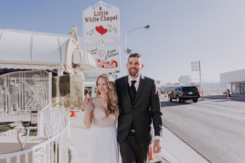 bride and groom smile as they walk down the street with little white chapel neon sign behind them