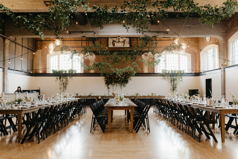 indoor reception space with greenery garlands hanging from the ceiling