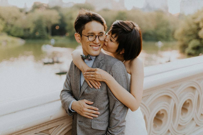 Asian couple smiling hugging while standing on bridge in Central Park