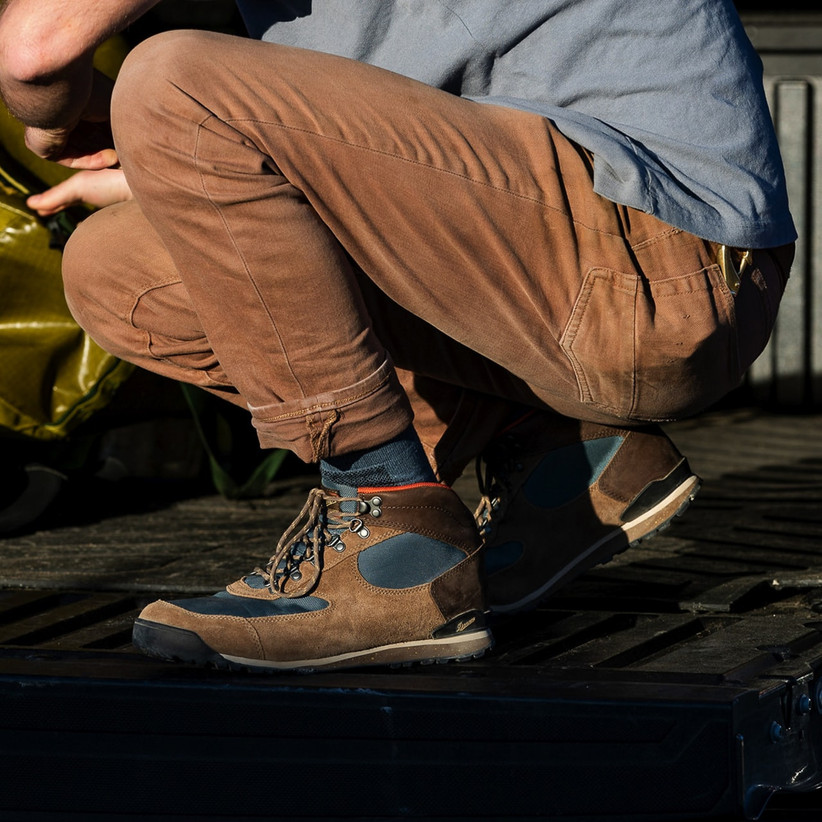 Cloe up of man crouching down wearing stylish high-ankle hiking boots