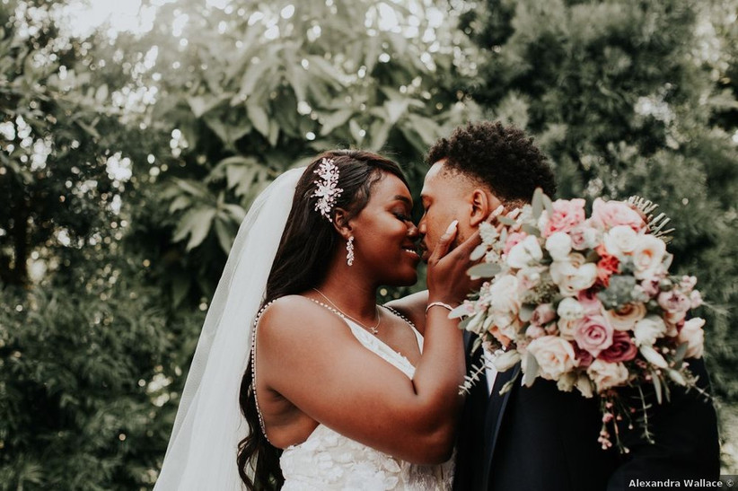Black couple looks into each other's eyes while smiling. The bride is wearing a veil and has her hand on his cheek