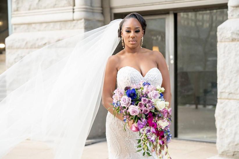 Black bride holding purple and blue cascade flower bouquet