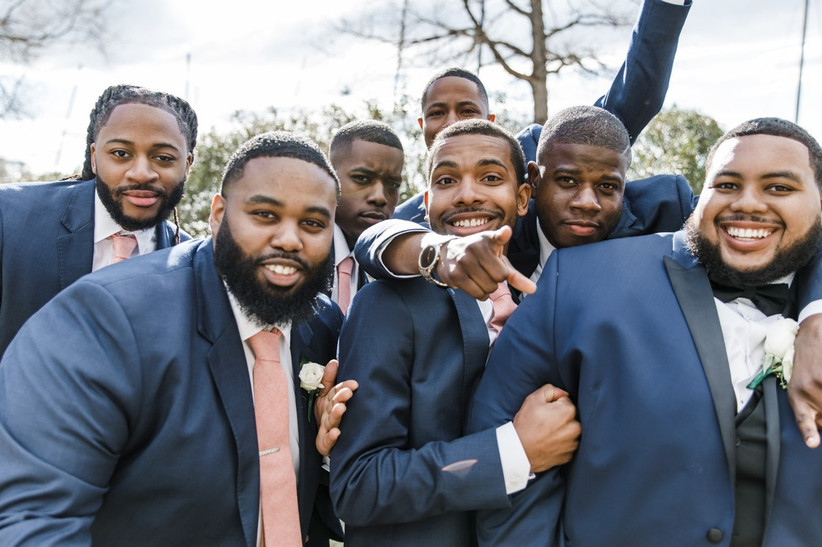 groom and his groomsmen gather for a huddle and wear matching blue tuxedos