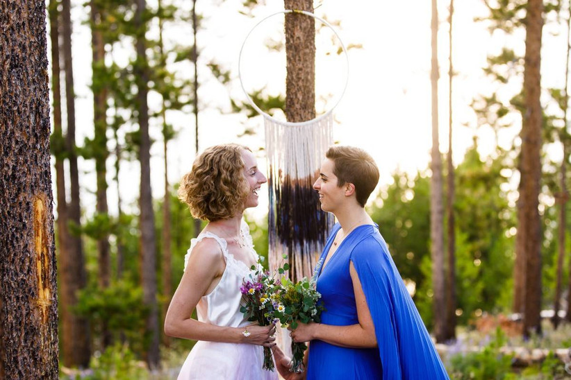 two brides standing in front of tie-dye wedding hoop backdrop decorated with ribbons
