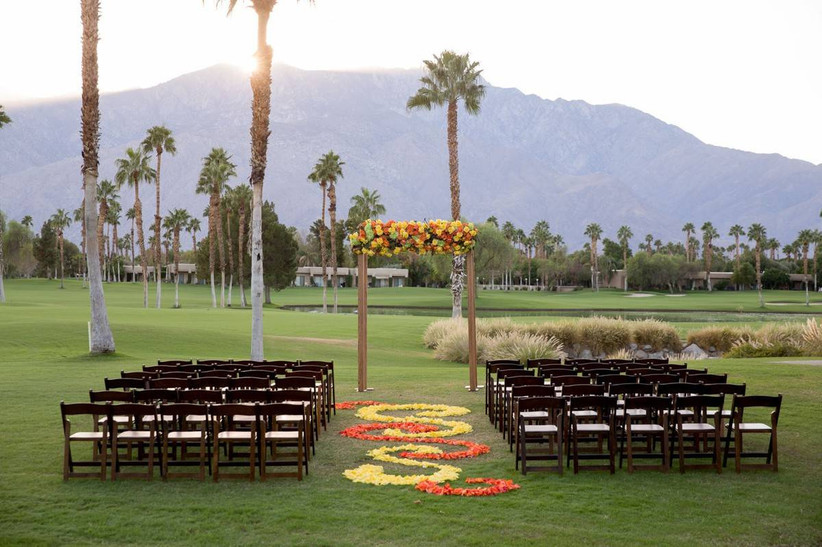 outdoor wedding ceremony on golf course with mountain backdrop and colorful floral aisle
