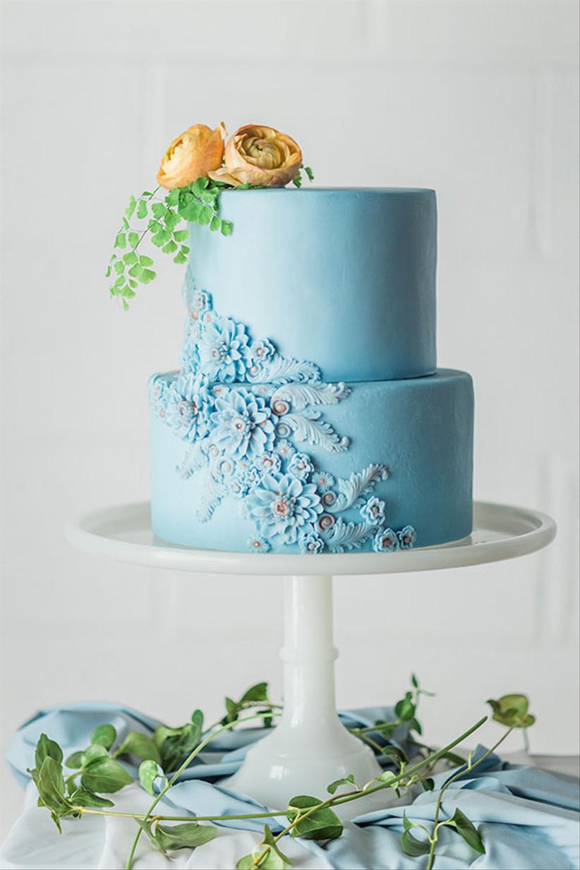 light blue wedding cake decorated with sugar flowers and fresh orange ranunculus