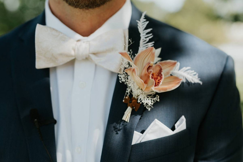 groom wearing charcoal gray suit and orange orchid boutonniere