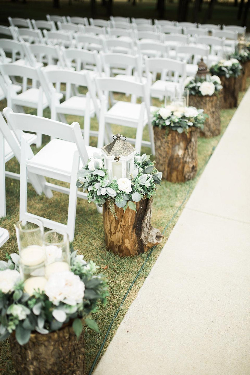 rustic outdoor wedding aisle decor eucalyptus bundles and floating candles in glass vases on top of sliced tree stumps