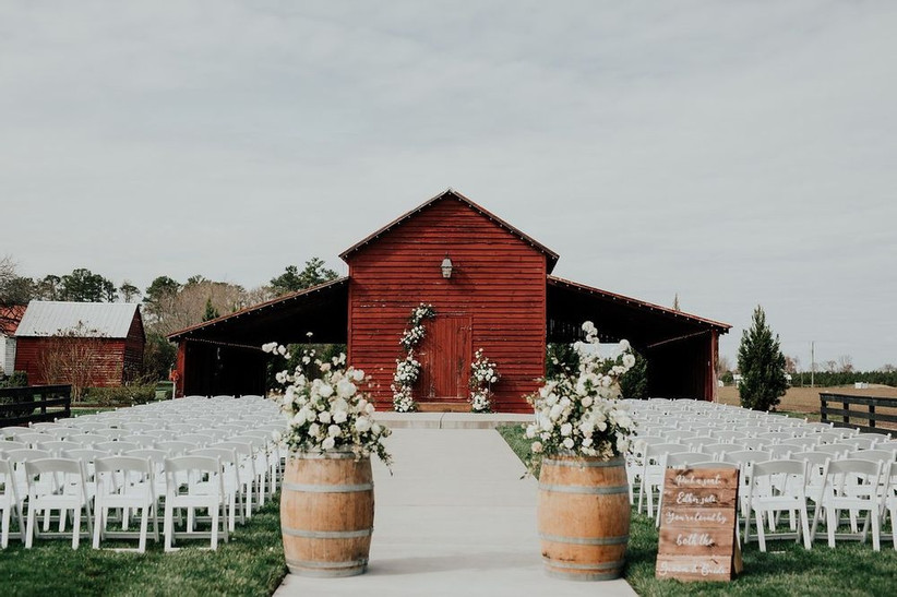 rustic outdoor wedding aisle decor flower arrangements on top of wine barrels on both sides of the aisle