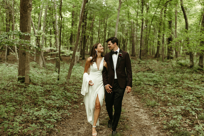 bride and groom walking arm in arm in the woods