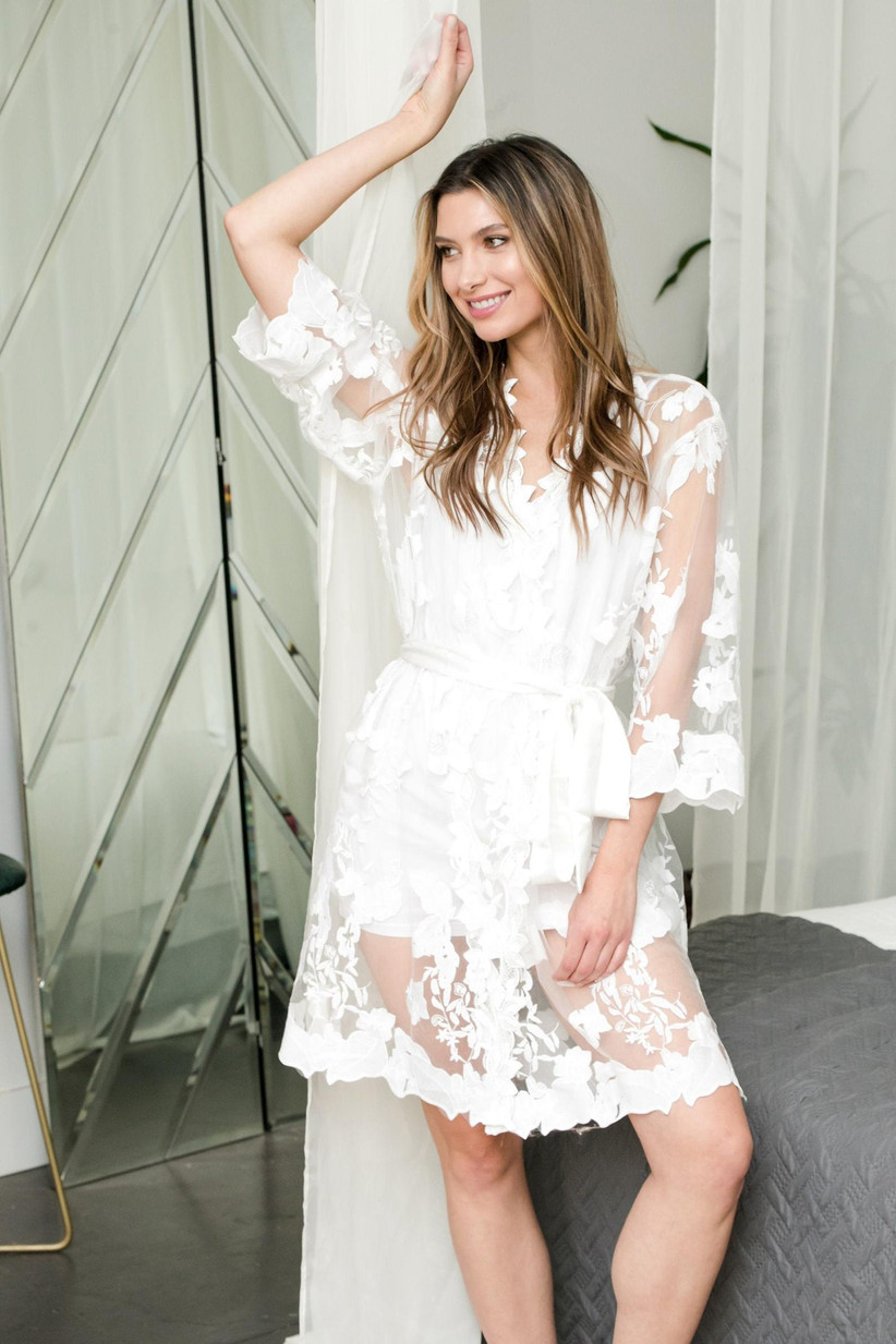 Model wearing sheer white robe with romantic floral details