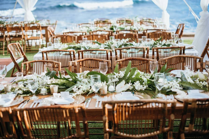 simple beach wedding centerpiece tropical greenery and white orchids along the center of long wooden banquet tables