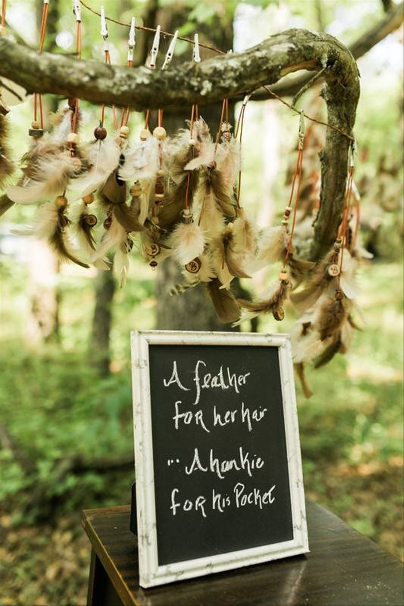 chalkboard wedding favors sign in front of handmade feather hair accessories hanging on a branch