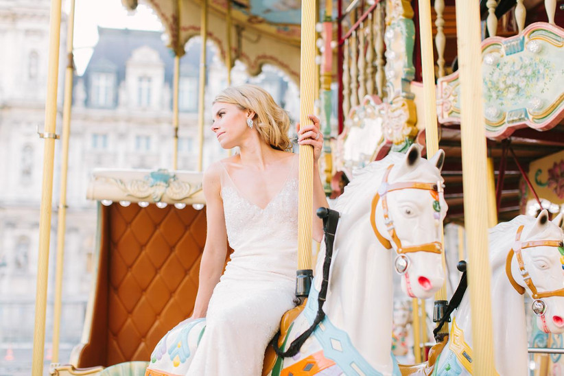 bride sitting on a carousel in paris looking off into the distance