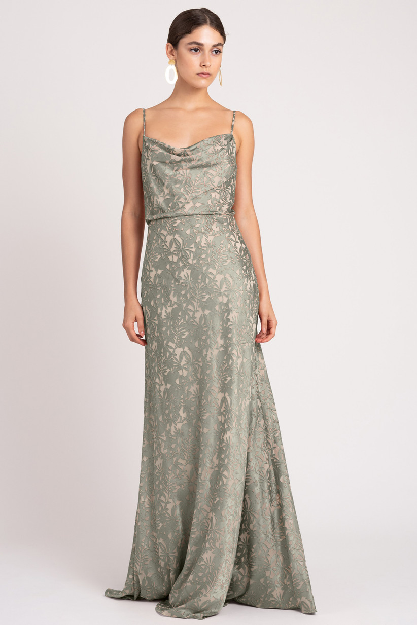 Model wearing elegant sage green mermaid gown with burnout satin creating an abstract floral pattern