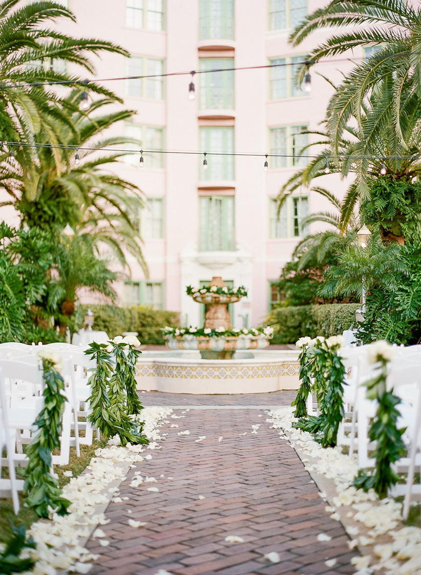 outdoor wedding ceremony at brick courtyard with stone fountain at the alter and white rose petals lining the aisle
