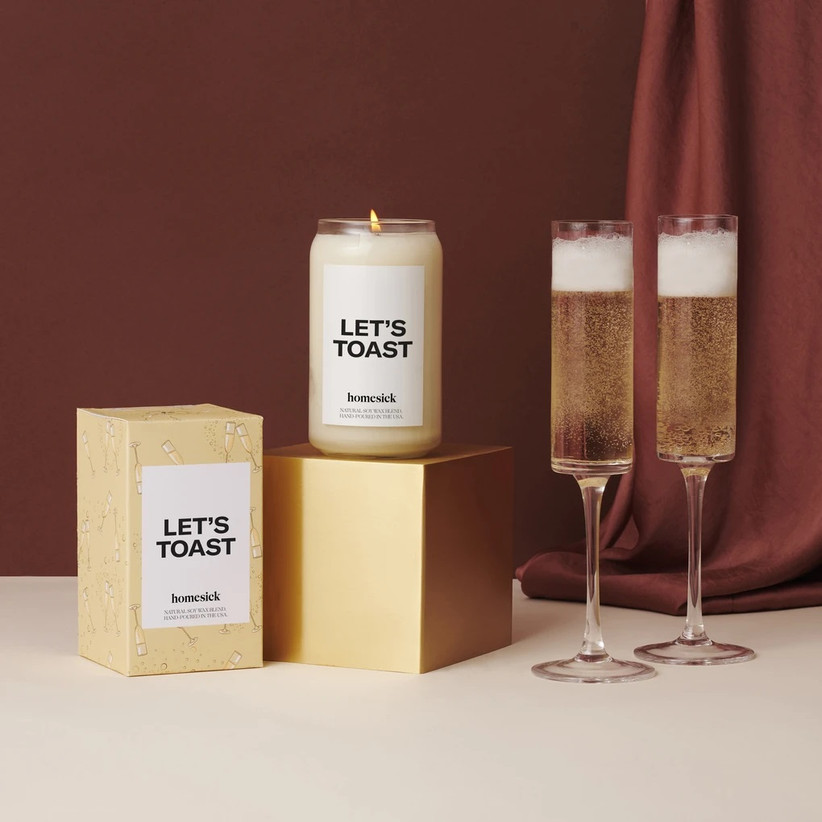 Let's Toast scented candle next to two glasses of champagne