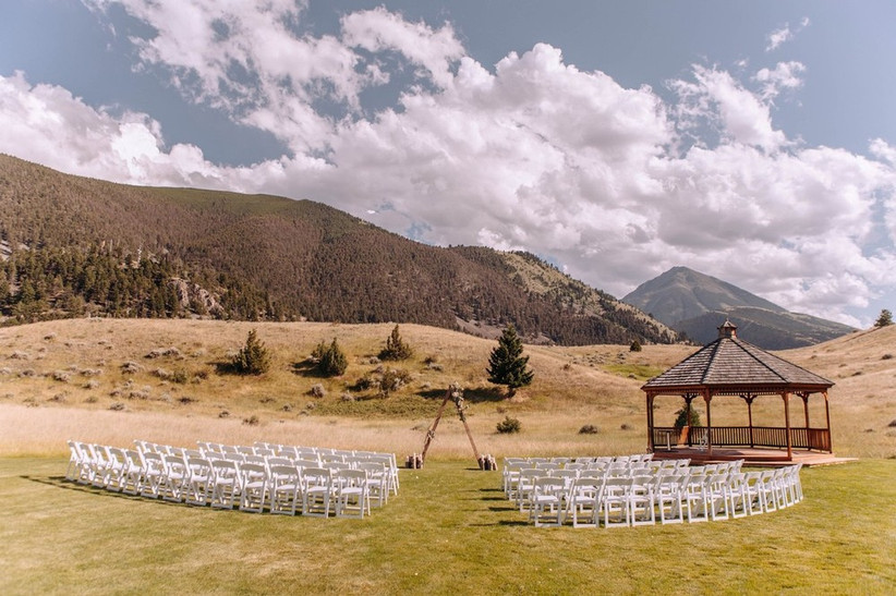 rows of chairs are set up for outdoor wedding ceremony with mountains in the background