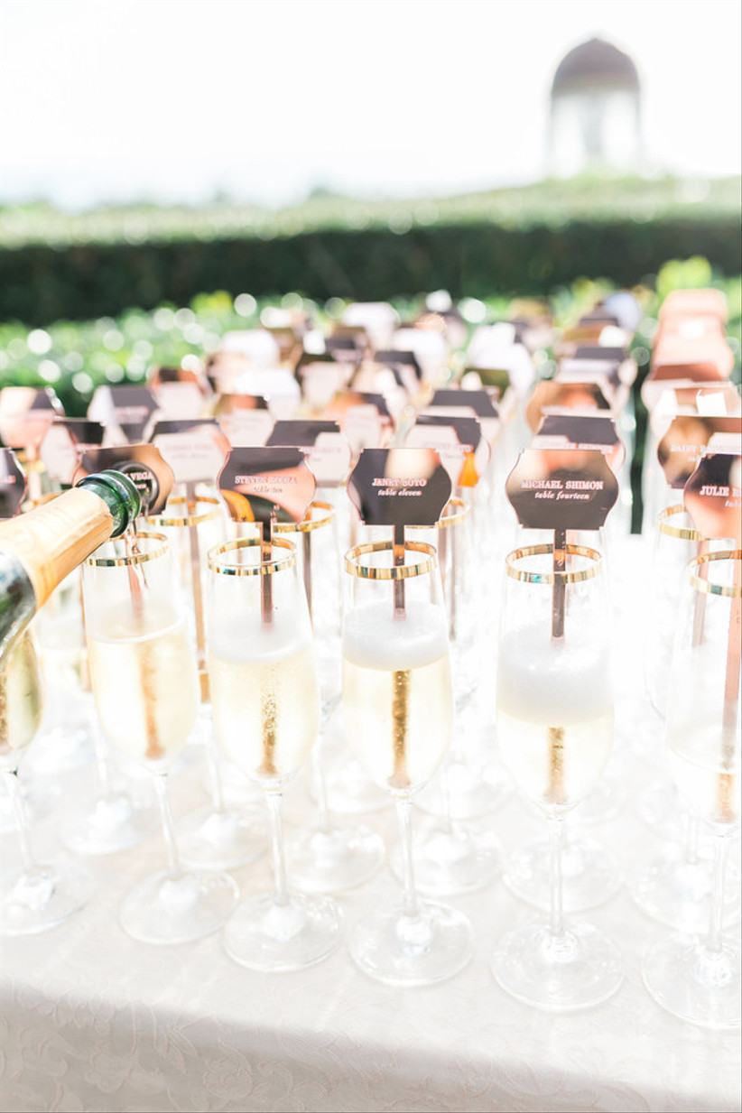 champagne flute wedding escort cards with stir sticks engraved with guests names