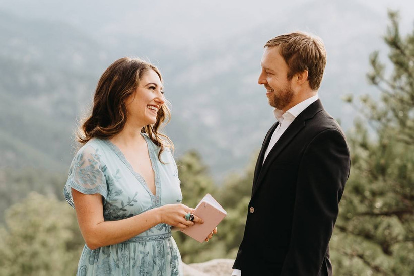 bride and groom at outdoor elopement location with mountain views behind them