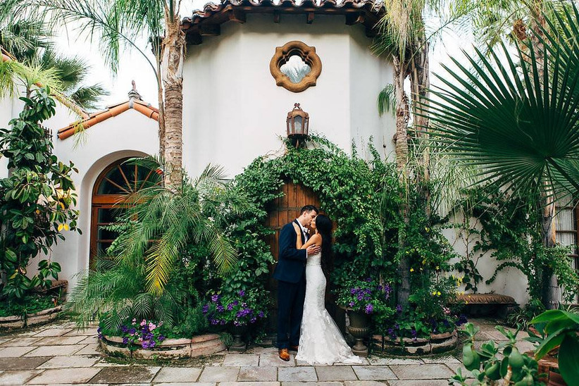wedding couple kissing in front of spanish style home