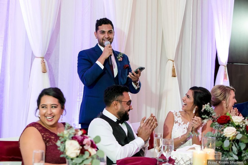 Best man stands up at the reception and reads his speech from his phone as the newlywed couple and guests laugh