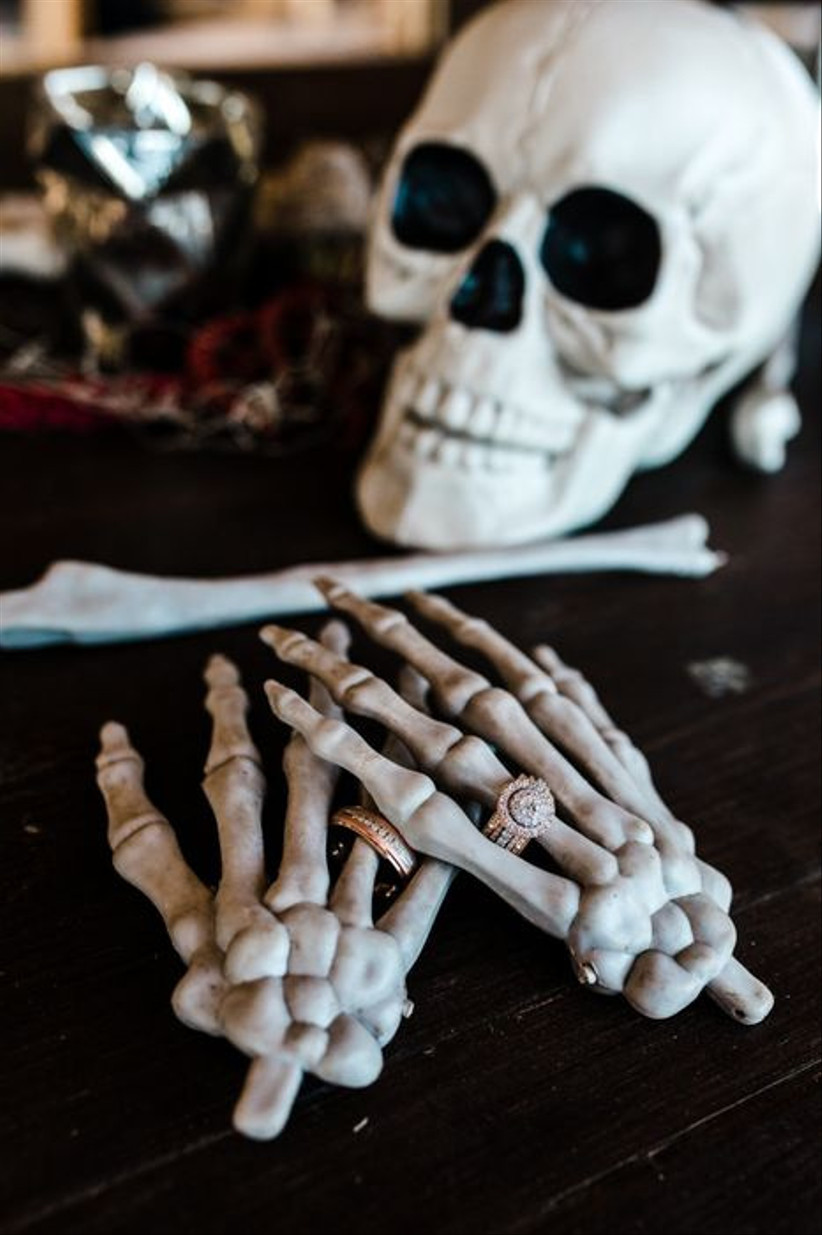 halloween themed wedding idea detail photo of skeleton hands with wedding rings